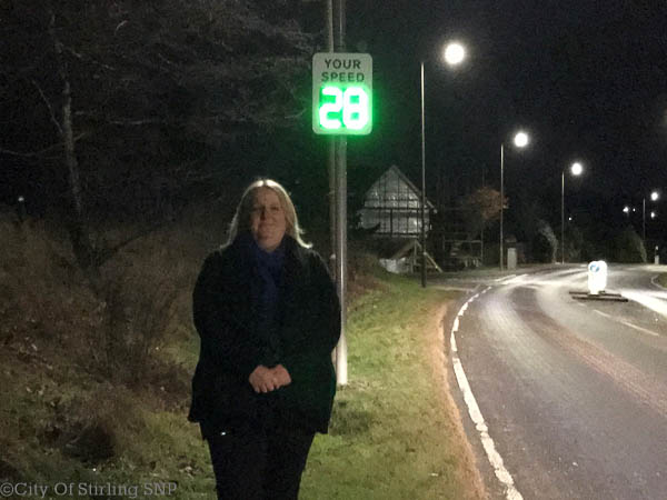 Alison stands in front of the newly deployed sign